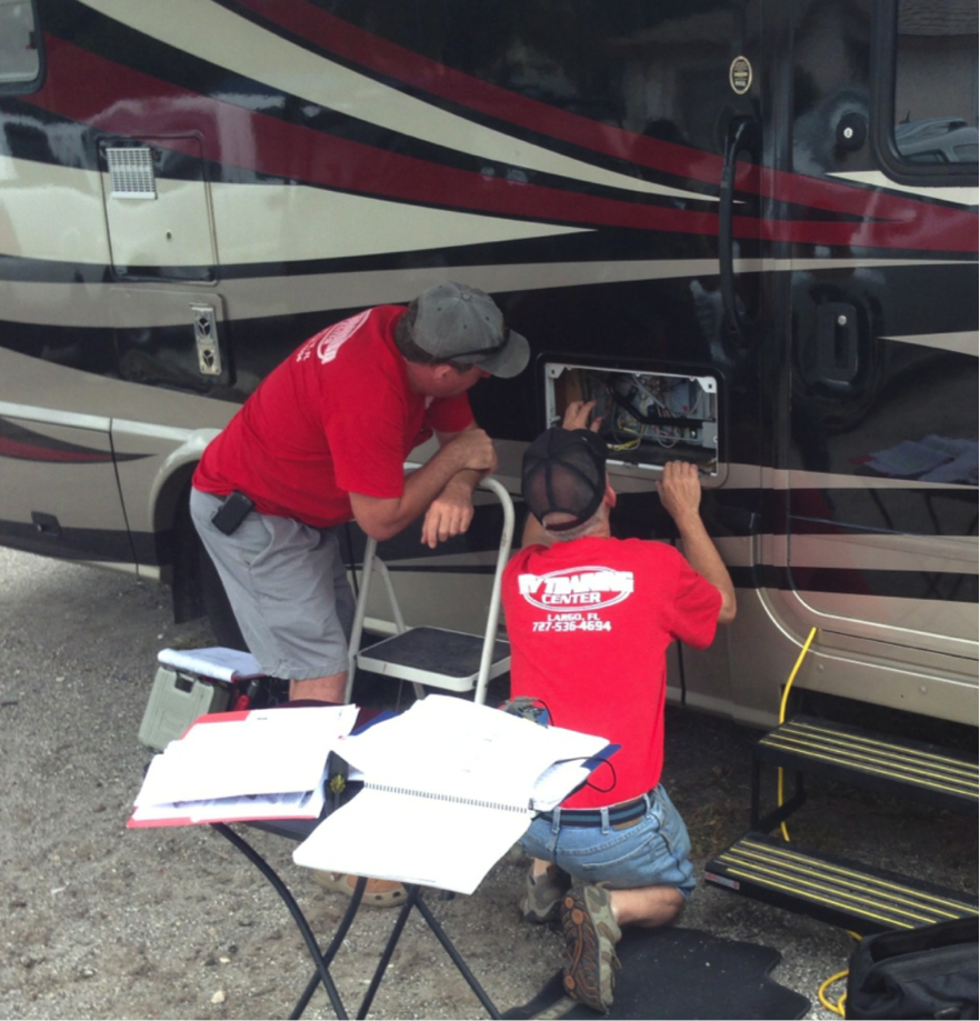 A pair of RV techs works on a motorhome at the RV Training Center's hands-on facility in Sweetwater, Fla.